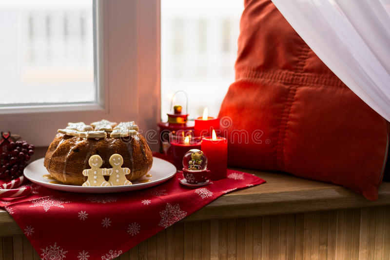 Christmas decoration: cake, gingerbread-men and burning red candles royalty free stock images