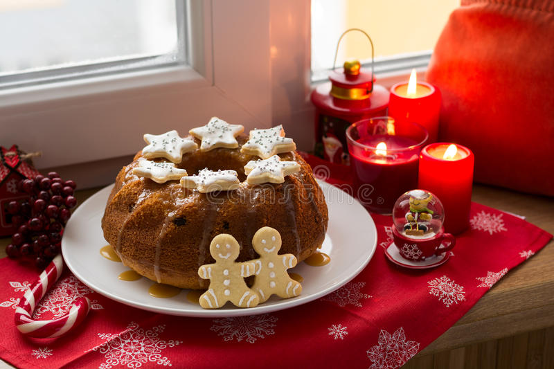 Christmas decoration: cake, gingerbread-men and burning red candles stock photo