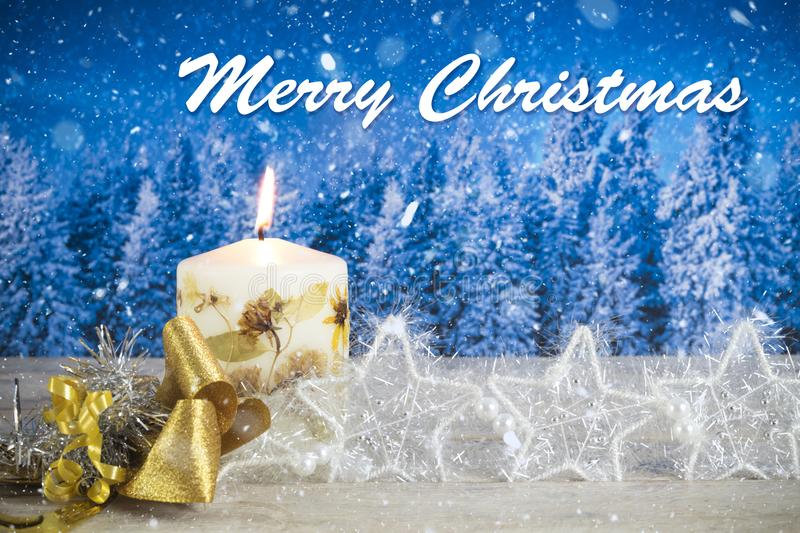 Christmas decoration with candle, golden bow, silver stars, with text in English `Merry Christmas` in a blue forest background.  stock photography