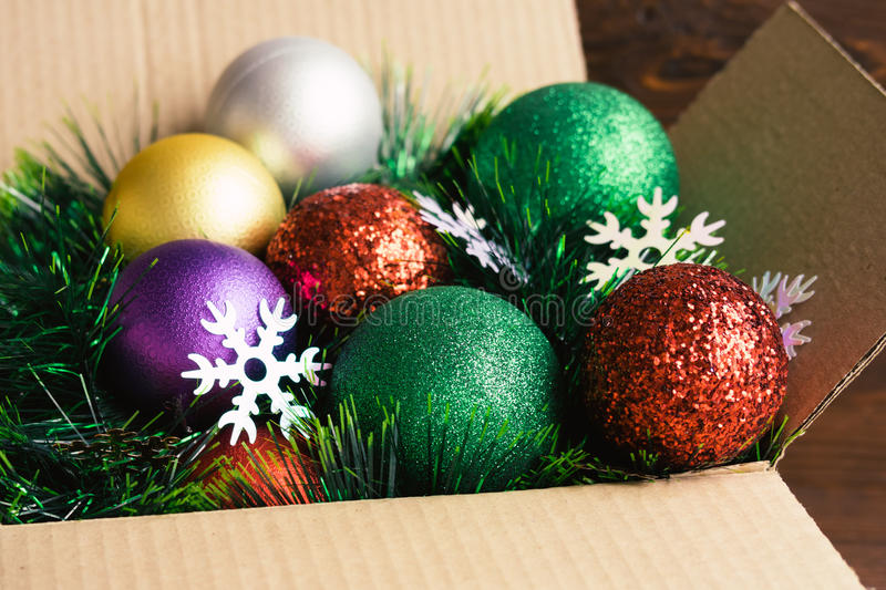 Christmas decoration in a cardboard box on a wooden background c royalty free stock image