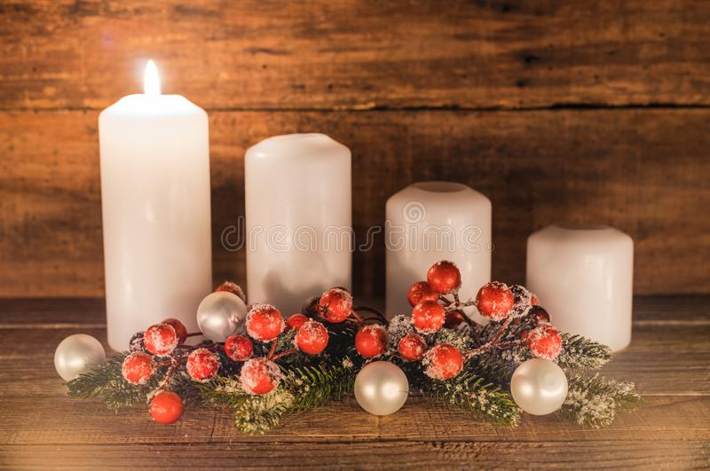 First Advent. Christmas decoration with christmas bauble, red berries, fir branches and candles for Advent season one candle burning stock photo