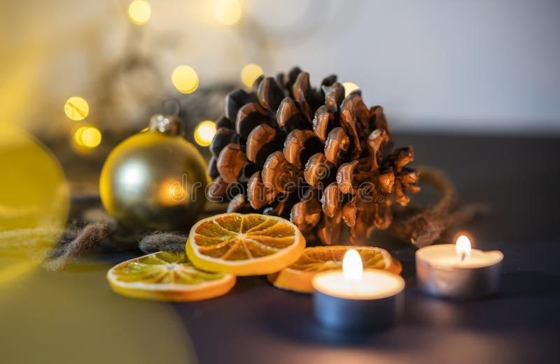 Christmas decoration closeup of a pinecone with candel, christmas ball and string lights on a blurry background stock photography