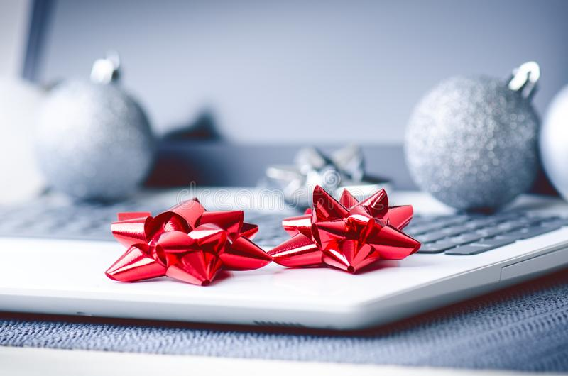 Christmas decoration on a computer. Laptop on a wooden table and white wall. Business concept during a holiday. Xmas concept. stock photos