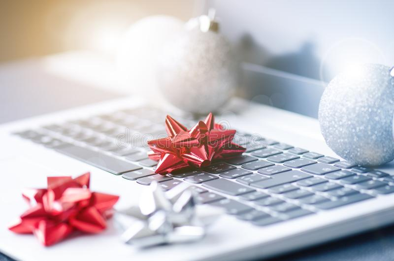 Christmas decoration on a computer. Laptop on a wooden table and white wall. Business concept during a holiday. Xmas concept. stock photography