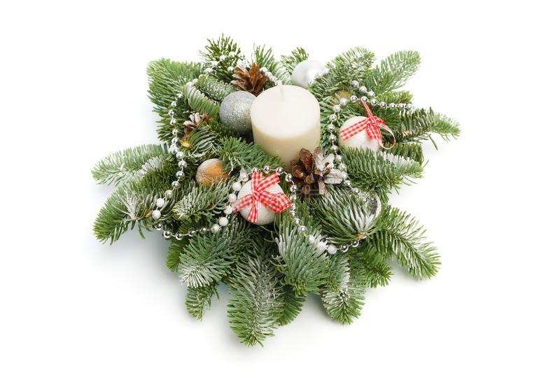 Christmas decoration consisting of fir twigs, shiny balls, cones around the candle, covered with snow on a white background stock images