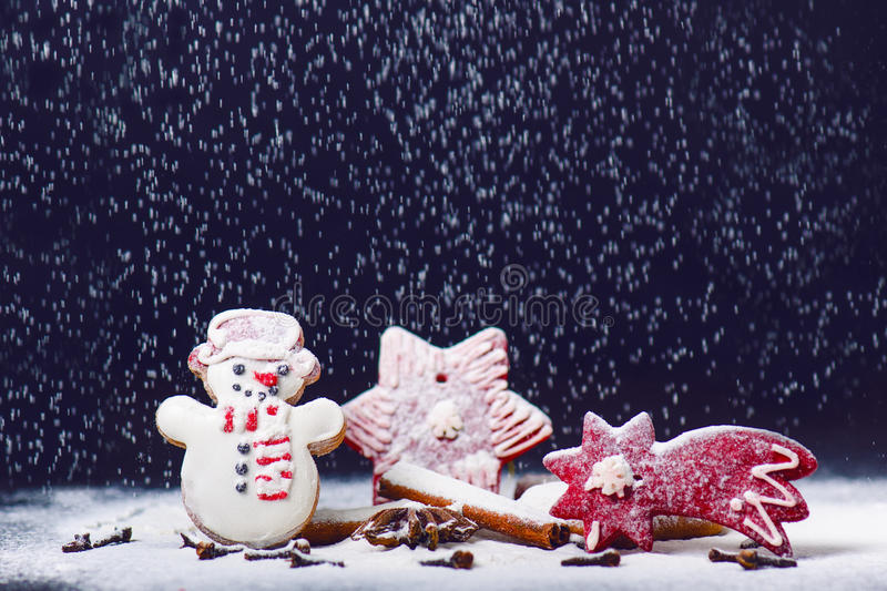 Christmas decoration and cookies.Woman hand sprinkling sugar on a cookies. Flour and spices for a baking on a dark backg. Christmas decoration and cookies.Woman stock image