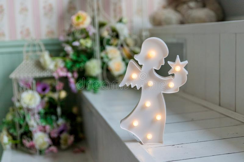 Christmas decoration. Figure of a little angel with star in hands isolated.angel lamp, decor for kids, wooden lamp in stock images