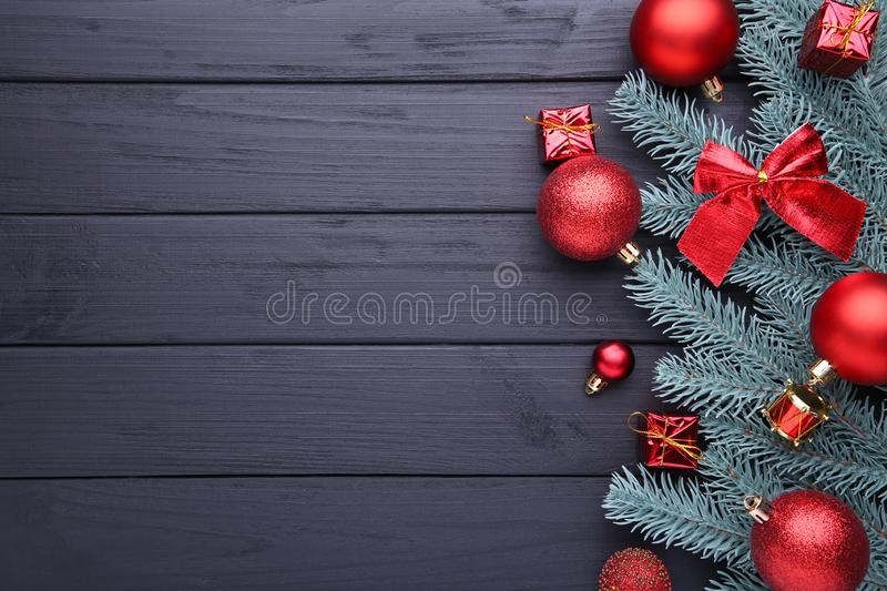 Christmas decoration. Fir-tree branch with balls, little gifts and bows on a black background royalty free stock photography