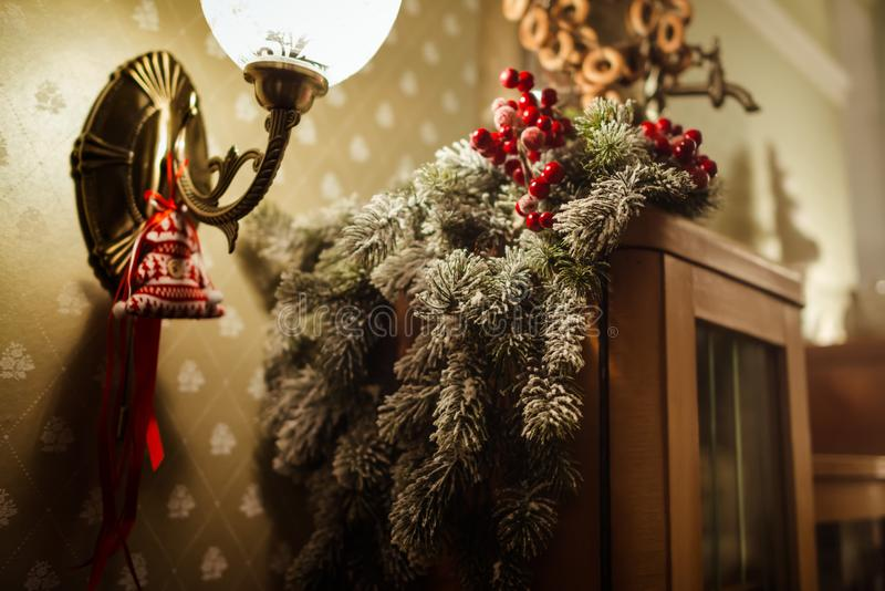 Christmas decoration with fir tree and holly berries as decor and lights with shadows. Close up stock photography