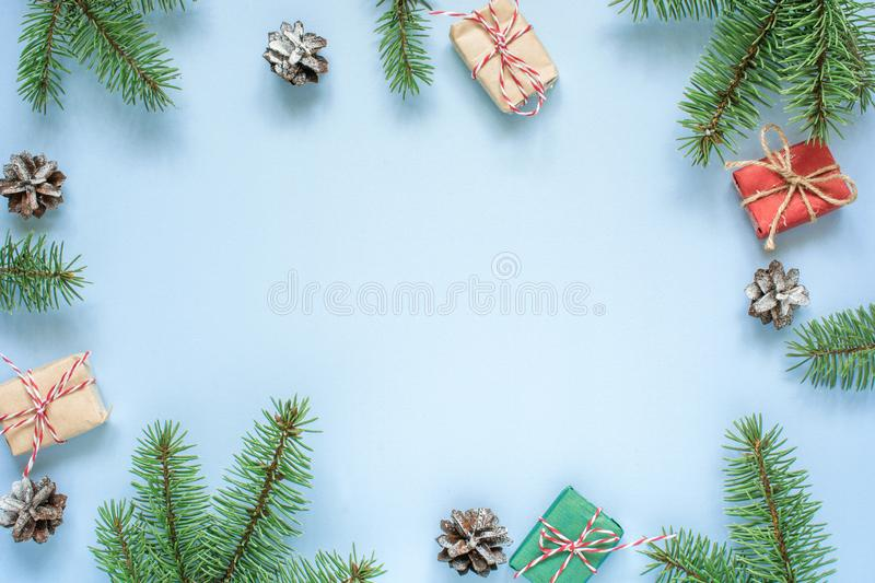 Christmas decoration. frame made of fir branches, star anise, decorations, gift boxes and pine cones on blue background stock images