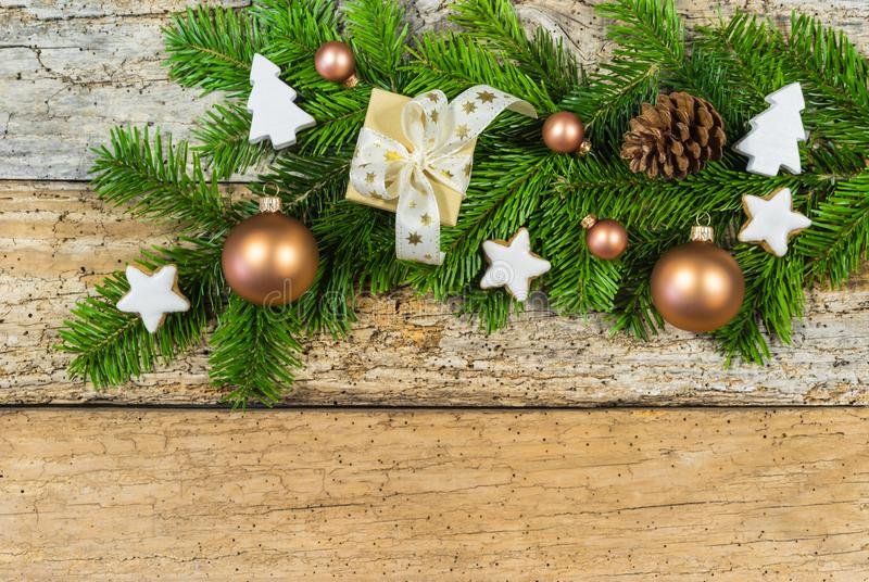 Christmas decoration with gift box, ornaments and fir branch on rustic wood background royalty free stock photo
