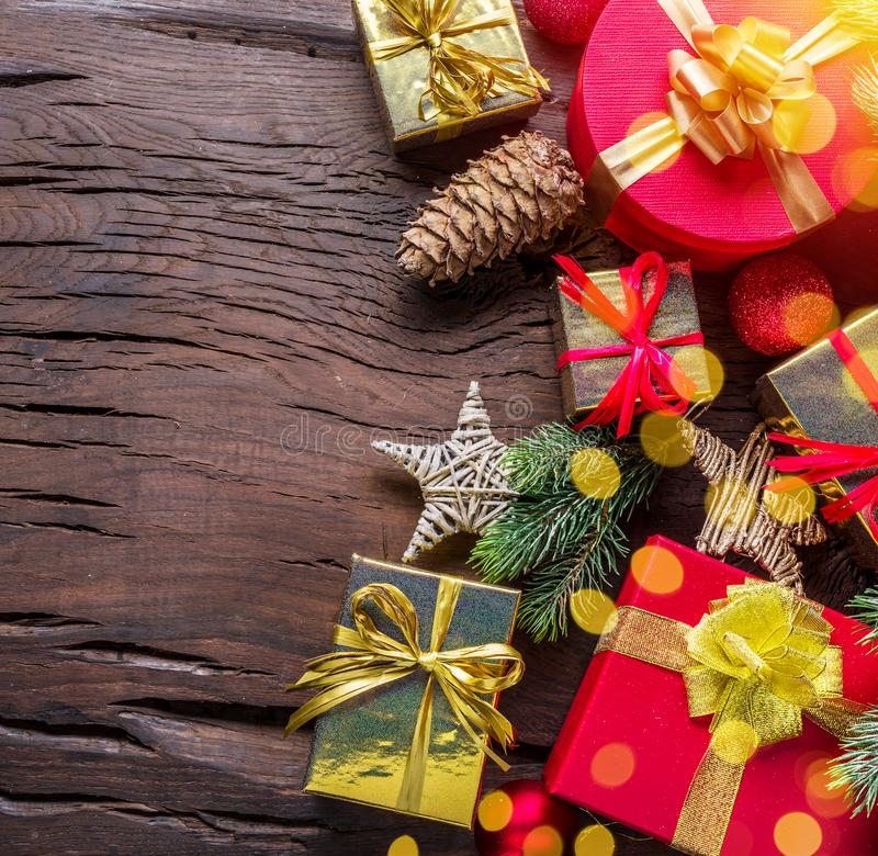 Christmas decoration, gift boxes and blurred lights on dark wooden table. Christmas or New Year holiday background shows the magic stock photography