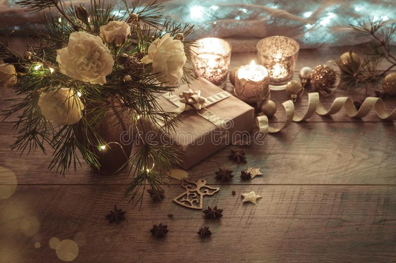 Christmas decoration. Gift, candles, lights, golden balls on a wooden rustic table. Composition of pine branches and stock image
