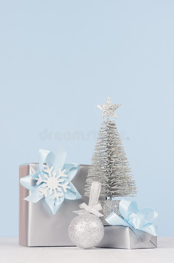 Christmas decoration and gifts in soft blue color - different metallic boxes with ribbons and bows, silver tree, glitter ball. Christmas decoration and gifts in stock photo