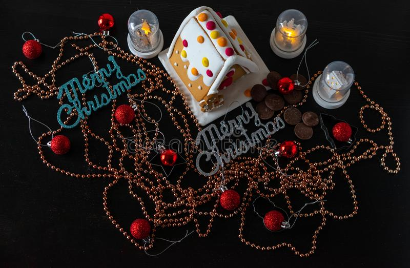 Christmas decoration with ginger bread house. Christmas ginger bread house with decorations around it. There are many bronze circular shiny beads with red royalty free stock image