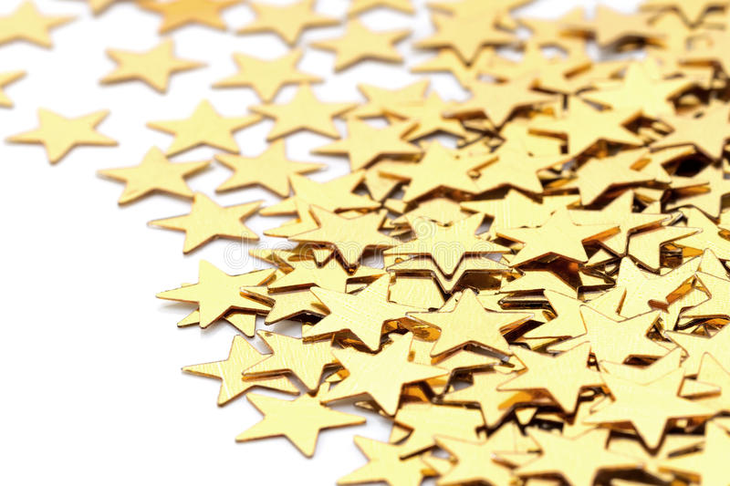 Christmas decoration of golden confetti stars against. White background royalty free stock image