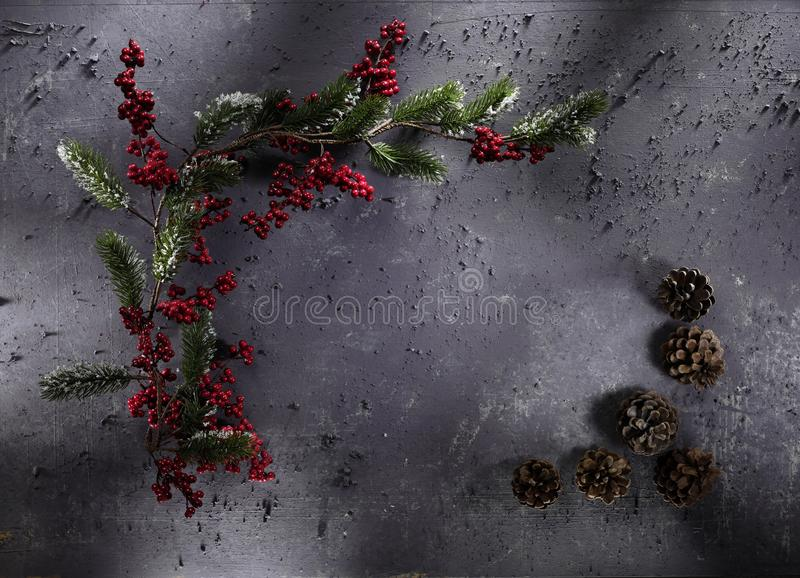 Christmas decoration on grey stone background. High-definition stillife photograpy dramatic light. shiny lightly object cone star green red gold golden royalty free stock image