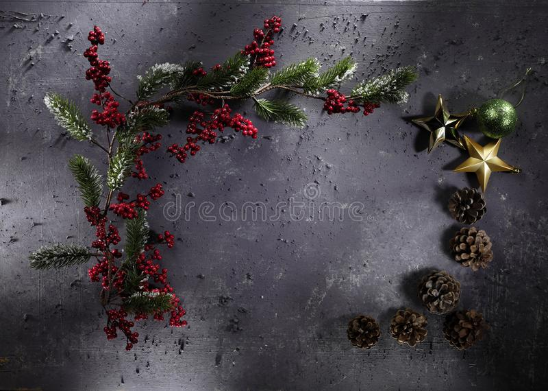 Christmas decoration on grey stone background. High-definition stillife photograpy dramatic light. shiny lightly object cone star green red gold golden stock photo