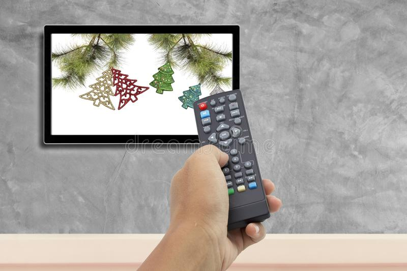 Christmas decoration with hand holding remote control at television screen with concrete wall royalty free stock photos