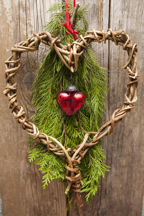 Christmas decoration with heart. Christmas decoration made by myself with green fir branches and red glass heart on an old wooden door royalty free stock photography