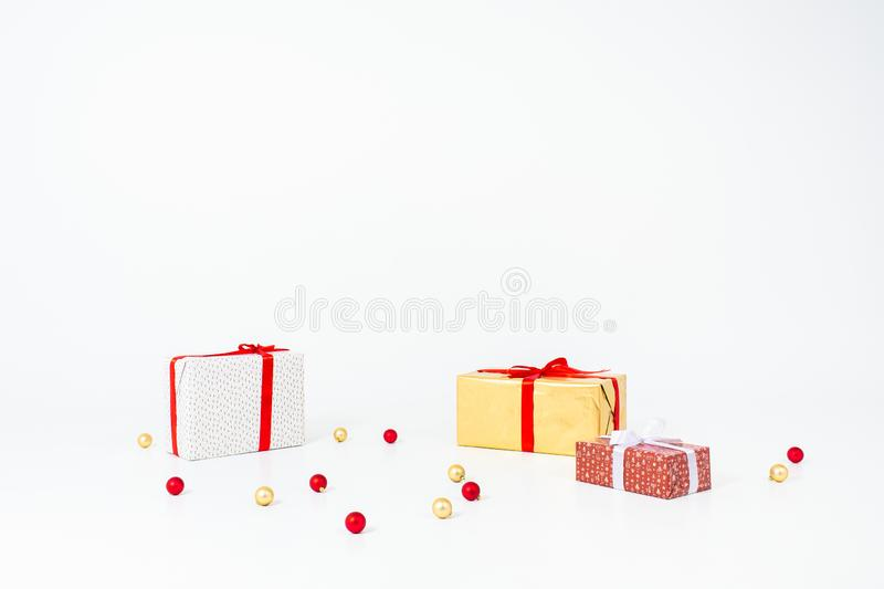 Christmas decoration isolated white. White and golden gift boxes with red ribbon with christmas balls. Copyspace. stock photos