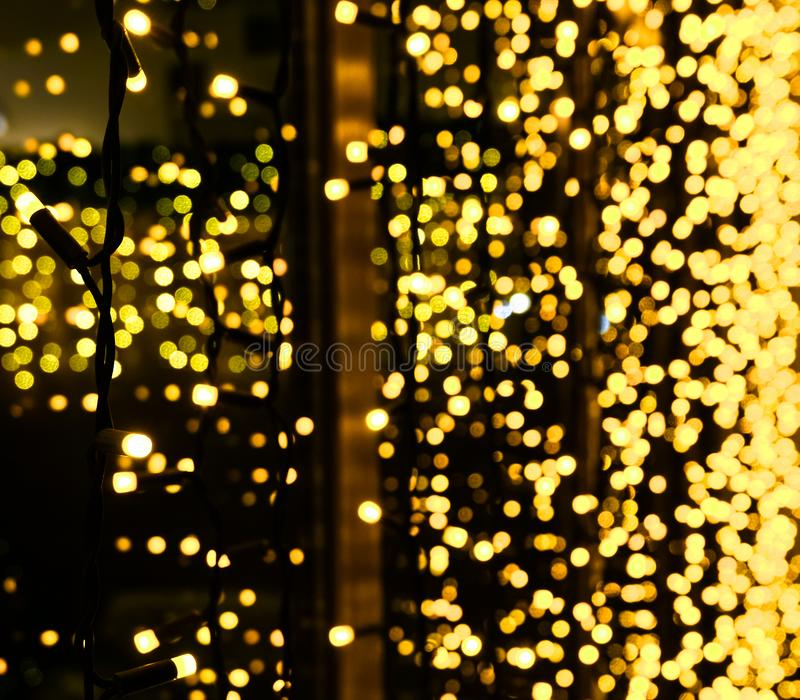 Christmas decoration made of glowing garland. New year illumination. Bright yellow and golden glitter lights background. Defocused.  stock image