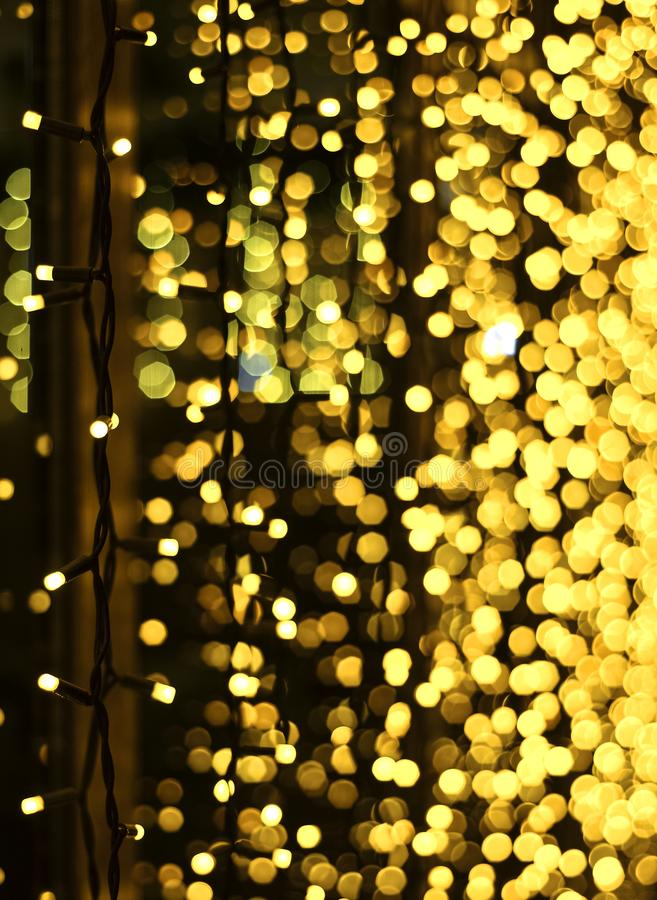 Christmas decoration made of glowing garland. New year illumination. Bright yellow and golden glitter lights background. Defocused. Shimmering light royalty free stock image