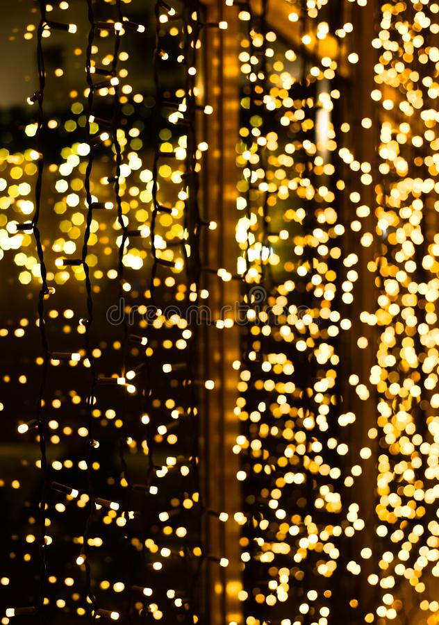Christmas decoration made of glowing garland. New year illumination. Bright yellow and golden glitter lights background. Defocused. Shimmering light royalty free stock photo