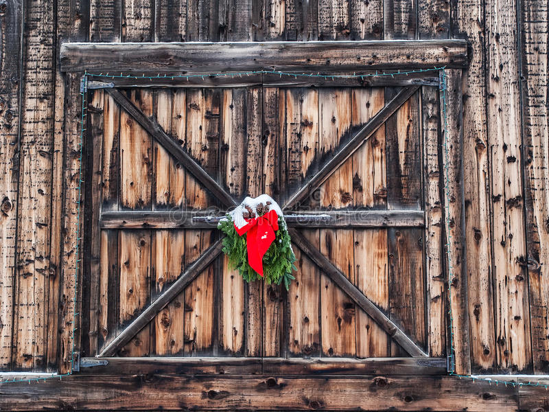 Christmas decoration on old barn. Christmas decoration of red ribbon and evergreen boughs hanging on old weathered barn door and covered with snow in royalty free stock photos