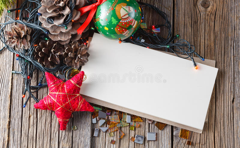 Christmas decoration with pine and cones. Christmas decoration on rustic wooden table with empty note. Closeup view royalty free stock photos