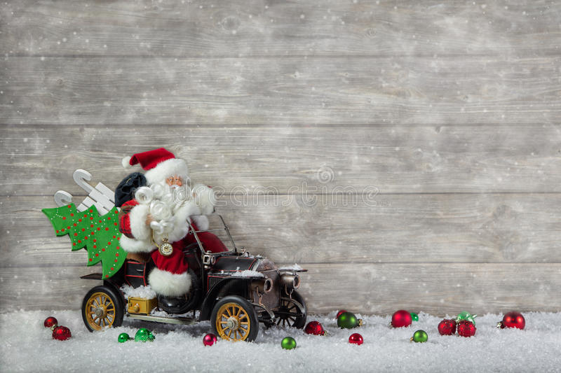 Christmas decoration: Red santa claus in hurry to buy christmas. Santa claus in rush with his car: christmas shopping stress. Decoration with old vintage tin royalty free stock images