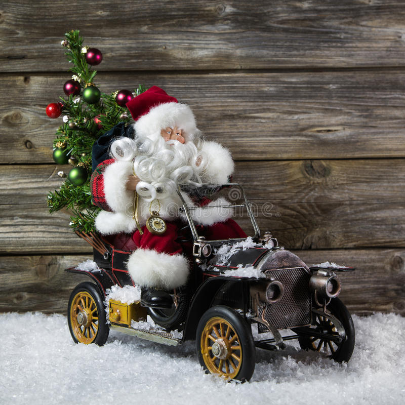 Christmas decoration: Red santa claus in hurry to buy christmas. Santa claus in rush with his car: christmas shopping stress. Decoration with old vintage tin royalty free stock photos