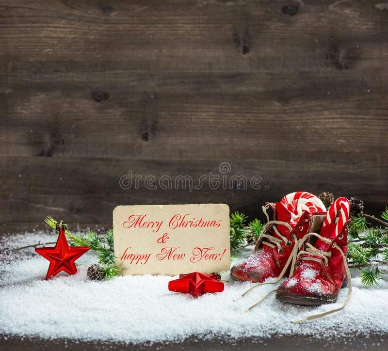 Christmas decoration red stars and antique baby shoes in snow. Vintage christmas decoration red stars and antique baby shoes in snow over wooden background royalty free stock photos