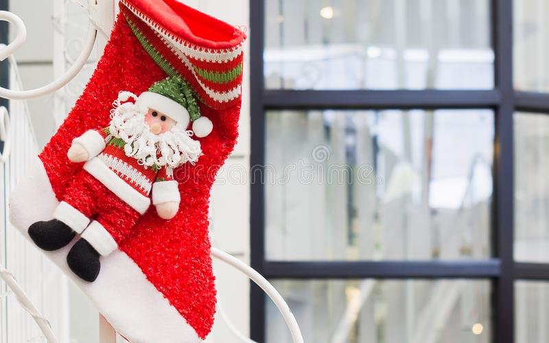 Christmas decoration red stocking and cute red santa claus toys. Hanging for xmas theme royalty free stock photography