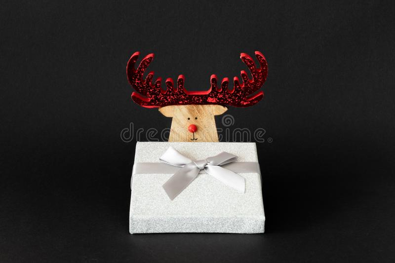 Christmas decoration reindeer with silver gift box on a black ba royalty free stock image