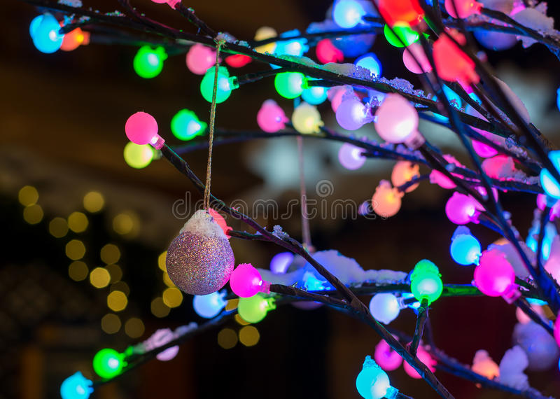Christmas decoration - shiny ball with tree of colorful lights stock photo