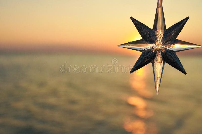 Christmas decoration star on the background of the sunset on the sea. Horizontal. stock images