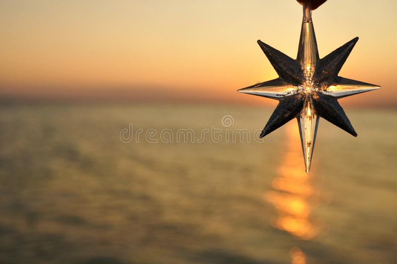 Christmas decoration star on the background of the sunset on the sea. Horiz stock images