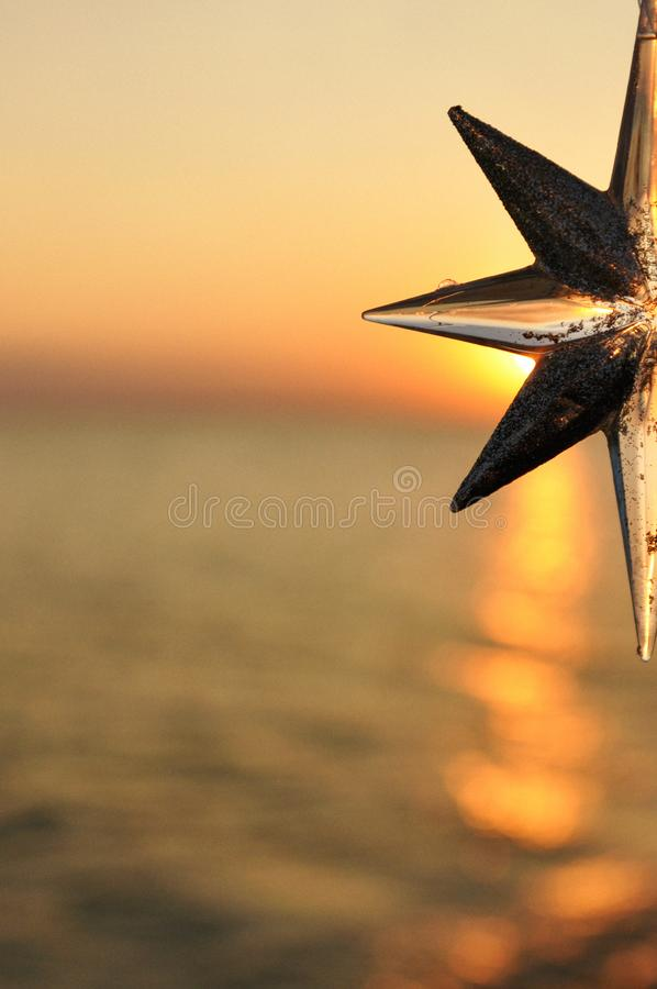 Christmas decoration star on the background of the sunset on the sea. Vertical royalty free stock photo