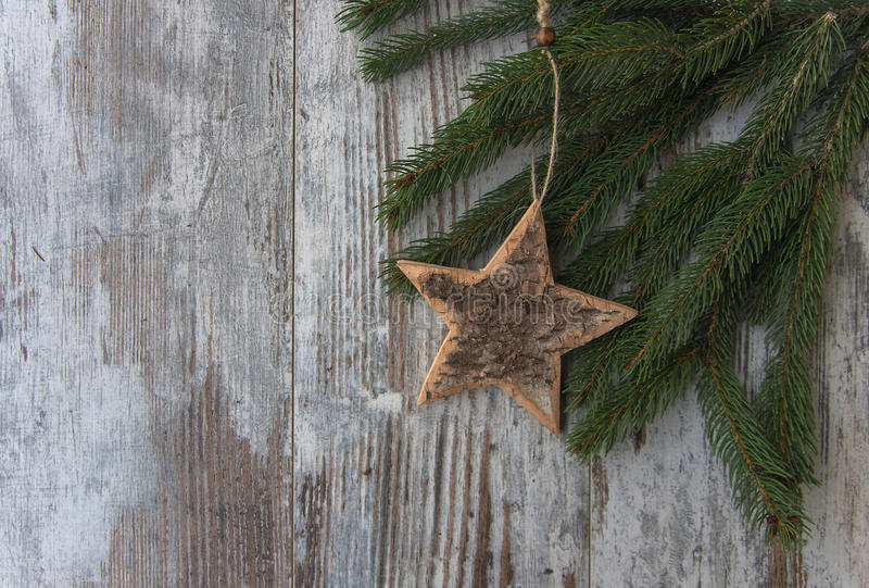 Christmas decoration, star and conifer of fir tree on textured w. Christmas decoration, heart on conifer of fir tree on textured wood background royalty free stock photography