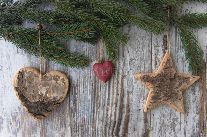 Christmas decoration, star and hearts, and conifer of fir tree o. Christmas decoration on wood background royalty free stock photo