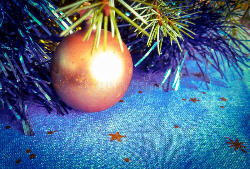 Christmas decoration on the table. Golden ball with fir tree branch Christmas decoration on starry tablecloth royalty free stock photo