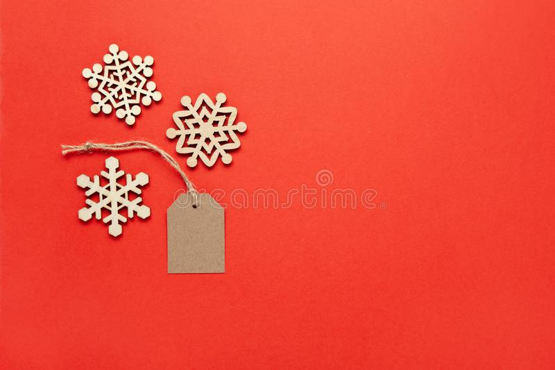 Christmas decoration, three little wooden snowflakes and craft tag on bright red background, copy space. Festive, New Year, sales. Concept. Horizontal, flat lay stock photo