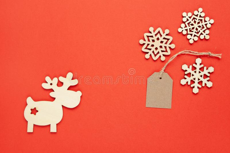 Christmas decoration, three little wooden snowflakes, craft tag, deer on bright red background. Festive, New Year, sales, eco stock photo