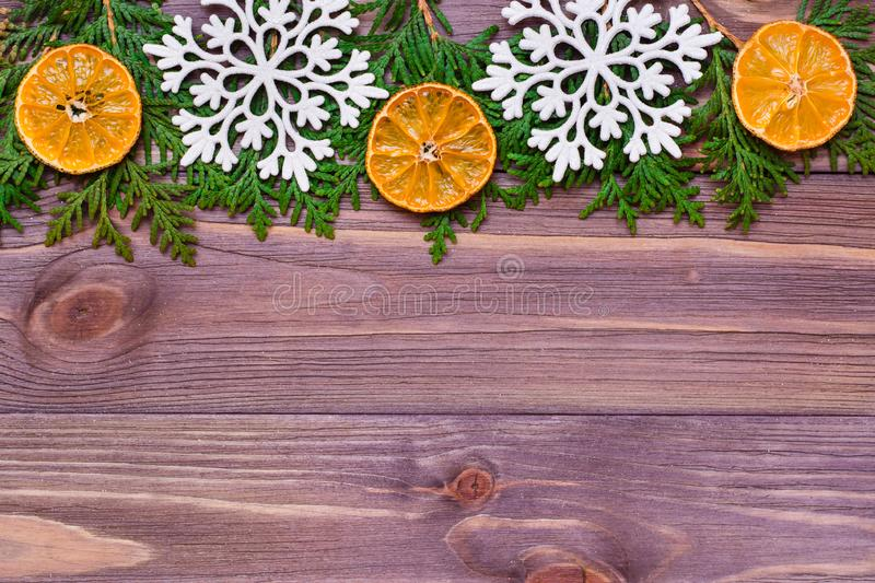 Christmas decoration with thuja branches, snowflakes and tangerines on wooden background stock images