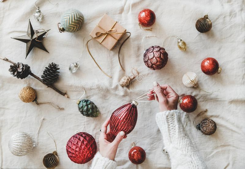 Christmas decoration toys and woman`s hands over beige linen cloth stock photos