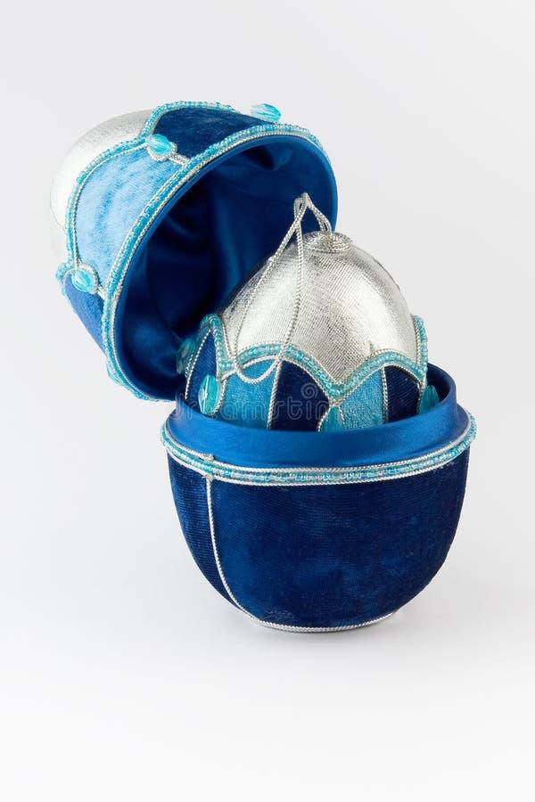 Christmas decoration velvet ball in case. Christmas decoration silver with blue velvet ball in case on gray background royalty free stock image