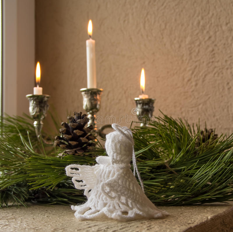 Christmas decoration on the window. A wreath, angel and candle as a symbol of offensive Christmas royalty free stock image