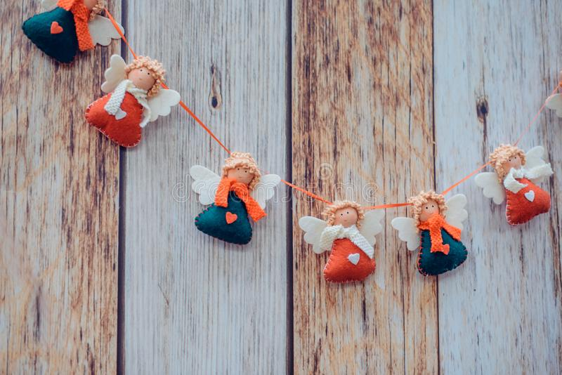 Christmas decoration on wooden background. Garland with hand made fabric angels. New year mock up. Selective focus, Copy space.  royalty free stock photo