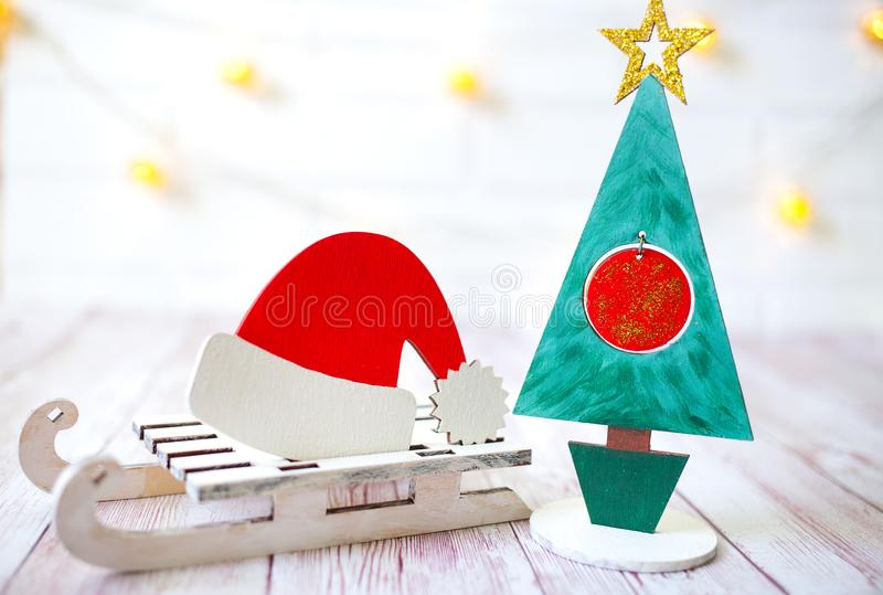 Christmas decoration on wooden background over white wall, close-up. Wooden christmas tree with Santa Claus hat on wooden sled royalty free stock photo